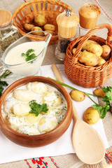 Tender young potatoes with sour cream and herbs in wooden bowl