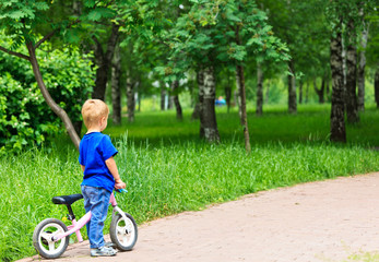 little boy with bike in the park