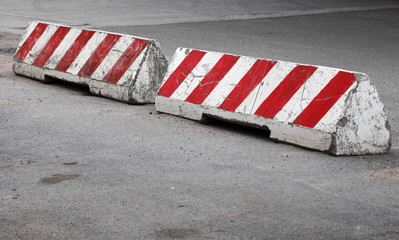 Red and white striped concrete road barriers
