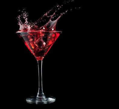 red cocktail splashing into glass on black