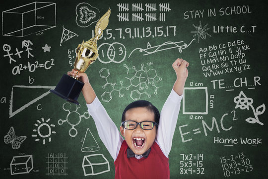 Happy student boy hold trophy in class