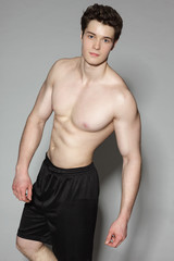 Handsome young muscular sports man on gray background