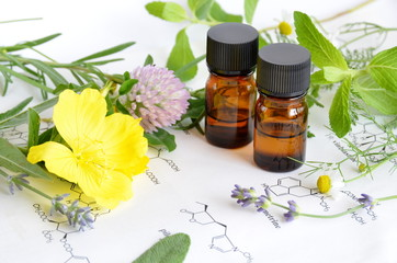 essential oils with herbs on science sheet