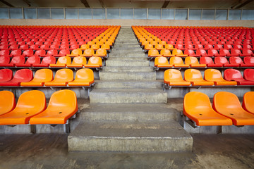 Aluminium Prints Stadion Rows of red and orange plastic sits at stadium