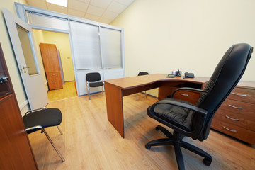 Interior of empty office cabinet with black armchair