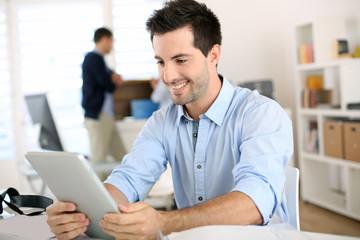 Smiling man in office working on digital tablet