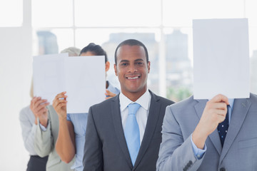 Businessman smiling at camera with colleagues covering faces