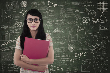 Confident female student standing in class