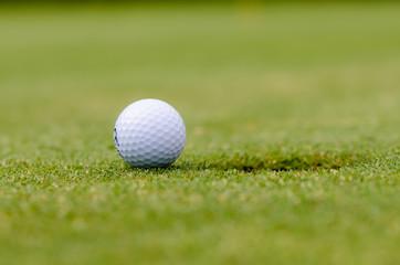 golfball liegt vor dem loch