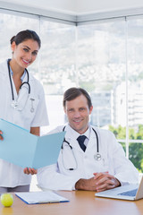 Smiling doctor showing a folder to a colleague