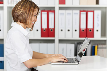 Side view of smiling businesswoman using laptop