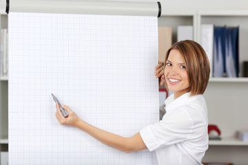 Woman writing on a blank flipchart