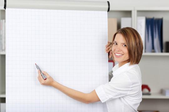 Woman writing on a blank flipchart