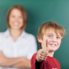 Young boy giving a thumbs up gesture