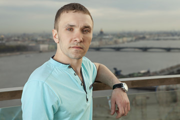 A young man in a turquoise shirt, short sleeve.