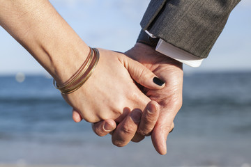 A couple holding hands by the sea.