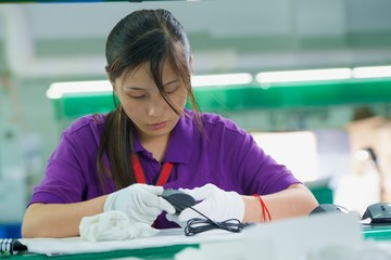 Female worker in white gloves assembling computer mouse