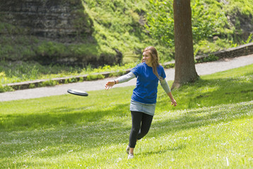 Young Girl Playing Frisbee At The Park