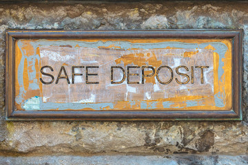 Weathered copper bank placard with the text safe deposit