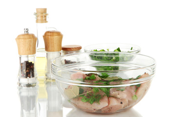 Chicken meat in glass bowl,herbs and spices isolated on white