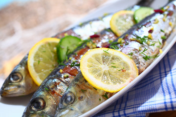 Close-up of grilled sardines on a platter outdoors