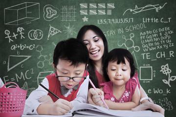 Beautiful teacher see children writing in class