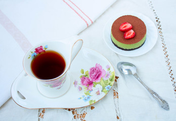 Tiramissu cake with strawberries and a cup of tea. top view