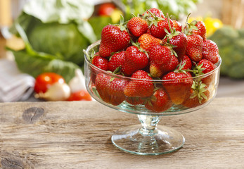 Glass bowl of fresh ripe strawberries on rustic wooden table