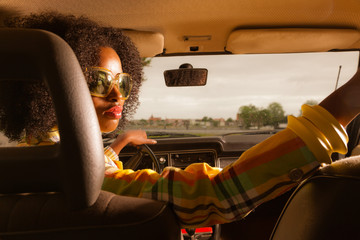 Retro 70s afro fashion woman with sunglasses driving in brown se