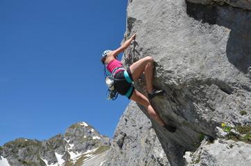 Frau klettert am Fels
