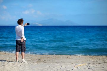 Man taking photo with cell phone on the beach