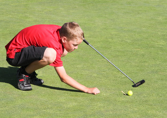 Young male golfer lining up putt