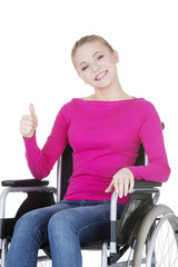 Attractive smiling disabled woman sitting in a wheel chair