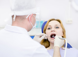 young woman with open mouth during drilling treatment