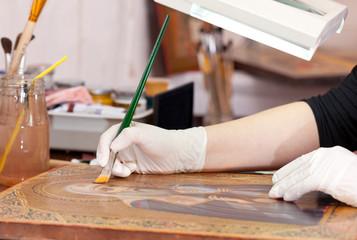 Art restorer works on old gilded icon