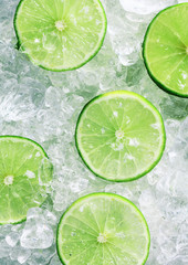 Slices of green limes over crushed ice cubes