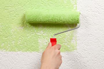 Maler streicht eine Wand mit Farbrolle