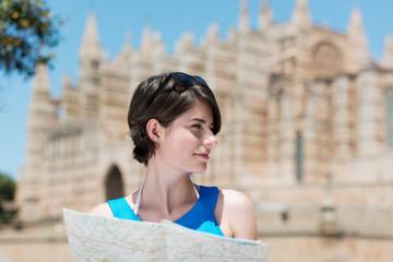 lächelnde touristin hält karte in der hand
