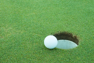 A golf ball very close to a hole