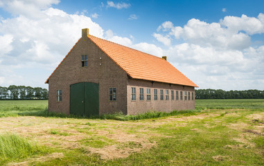 Old Dutch barn of brick masonry with an orange tile roof