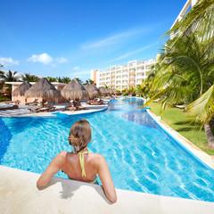 Woman in swimming pool at caribbean resort.