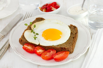 egg with black bread and tomato cherry