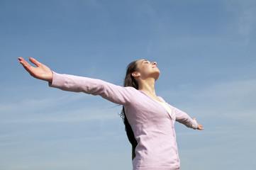 glückliche Frau mit ausgebreiteten Armen fühlt sich frei