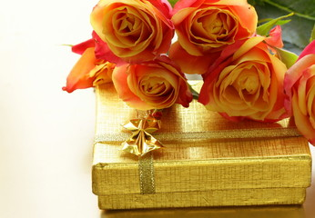 orange roses and box with gifts on gold background