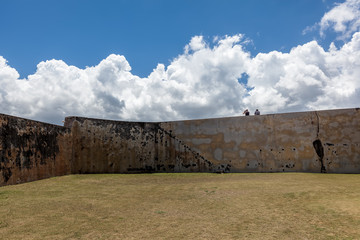 two people sit on wall at  El Morro in Old San Juan, PR