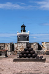cannonballs at  El Morro fort in San Juan, lighthouse in backgro