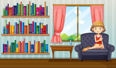 A girl sitting on a sofa holding a book inside the house