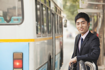 Young businessman waiting at the bus stop for the bus