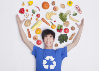 Young man with fresh fruit and vegetables, studio shot