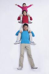Family sitting on each others shoulders, imitation, studio shot